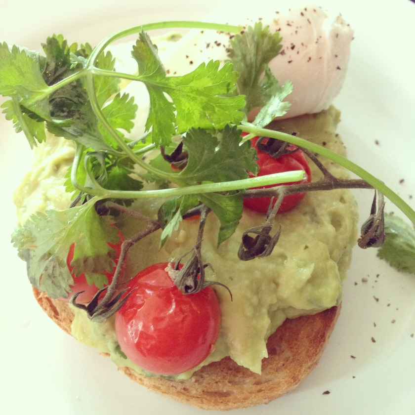 Smashed avocado on toast with a poached egg and roasted cherry vine tomatoes.